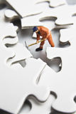 Worker figurine on puzzle pieces Royalty Free Stock Images