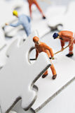 Worker figurine on puzzle pieces Royalty Free Stock Photo