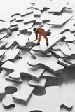 Worker figurine on puzzle pieces Royalty Free Stock Image