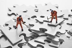 Worker figurine on puzzle pieces Stock Image