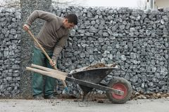Worker fill the wheel barrow Stock Photos