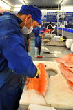 A worker is filleting salmon in a seafood supermarket in Vietnam Stock Photo