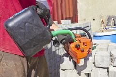 Worker filling fuel Into the chainsaw. Gasoline tool stock photography