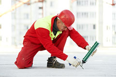 Worker filling joint with sealing foam. Builder filling joint of concrete board with industrial polyurethane sealing foam in protective workwear at construction Royalty Free Stock Images