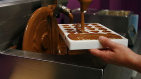 Worker filling mould with melted chocolate stock video