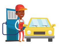 Worker filling up fuel into car. African-american gas station worker refueling a car. Gas station worker filling up fuel into car. Worker in workwear at the gas Stock Photography