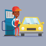 Worker filling up fuel into car. An african-american gas station worker filling up fuel into the car. Smiling worker in workwear at the gas station. Gas station Royalty Free Stock Image
