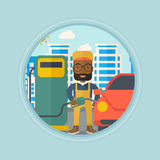Worker filling up fuel into car. An african-american worker filling up fuel into the car. Worker in workwear at the gas station. Gas station worker refueling a Royalty Free Stock Image