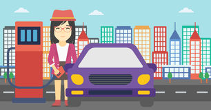 Worker filling up fuel into car. An asian woman filling up fuel into the car. Woman standing at the gas station and refueling a car. Vector flat design Stock Images