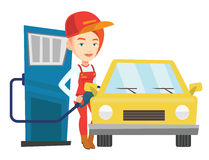 Worker filling up fuel into car. Caucasian worker filling up fuel into the car. Female worker in workwear at the gas station. Young gas station worker refueling Royalty Free Stock Photos