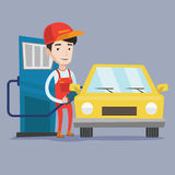 Worker filling up fuel into car. A friendly worker filling up fuel into the car. Smiling worker in workwear at the gas station. Gas station worker refueling a Stock Photo