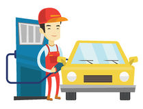 Worker filling up fuel into car at the gas station. Asian gas station worker filling up fuel into the car. Smiling worker in workwear at gas station. Young gas Royalty Free Stock Image