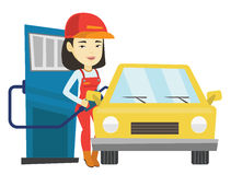 Worker filling up fuel into car at the gas station. Asian gas station worker filling up fuel into the car. Smiling worker in workwear at gas station. Young gas Stock Image