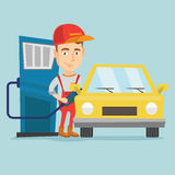 Worker filling up fuel into car at the gas station. Caucasian gas station worker filling up fuel into the car. Smiling worker in workwear at the gas station Royalty Free Stock Images