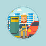 Worker filling up fuel into car. Hipster worker with beard filling up fuel into the car. Worker in workwear at the gas station. Gas station worker refueling a Stock Image