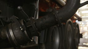 Worker fills fuel truck with steel pipe equipment