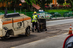 Worker fills a handbarrow with bitumen and Asphalt Paver Machine stock photography