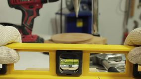 The worker finds the right level with the spirit level in the workshop stock video footage