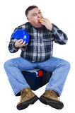 A worker finishes his hamburger. A worker ends his hamburger holding his helmet. White background Royalty Free Stock Photography