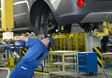 The worker fixes a detail to the car bottom. Assembly conveyor o. F automobile plant Stock Photo