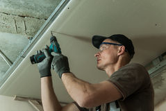 Worker fixes the drywall. To metal frame using screws Royalty Free Stock Image