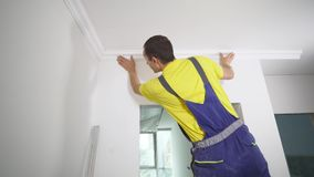 Worker fixes the plinth to the ceiling.  Stock Images
