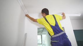 Worker fixes the plinth to the ceiling.  Stock Photo