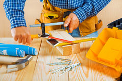 Worker fixes two wooden planks Royalty Free Stock Image