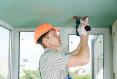 Worker is fixing the drywall. Worker is fixing the drywall to the ceiling with screwdriver Royalty Free Stock Photo