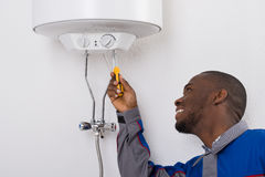 Worker Fixing Electric Boiler With Screwdriver. Happy Young African Male Worker Fixing Electric Boiler With Screwdriver Stock Photo