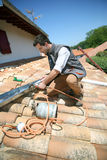 Worker fixing gutter on roof Royalty Free Stock Photo