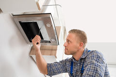 Worker Fixing Kitchen Hood Royalty Free Stock Image
