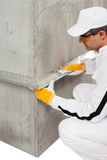 Worker fixing a lath on a corner Royalty Free Stock Images