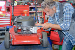 Worker fixing lawn mower Royalty Free Stock Images