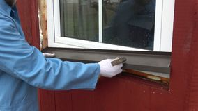 Worker fixing new window sill sheet metal on house stock footage