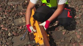 Worker fixing screw nut on railway track. In summer day stock video footage