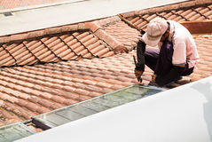 Worker fixing solar water heater on roof during maintenance Royalty Free Stock Photo
