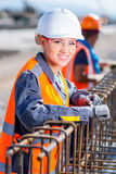 Worker fixing steel rebar at building site. Builder worker wires for knitting metal rods at the construction site Stock Photography