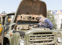 Worker Fixing Vehicle Engine. A road repair worker in Ufa Russia fixing a broken down vehicle in the hot summer sun of Bashkortostan Stock Photo