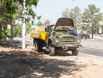 Worker Fixing Vehicle Engine. A road repair worker in Ufa Russia fixing a broken down vehicle in the hot summer sun of Bashkortostan Royalty Free Stock Photography