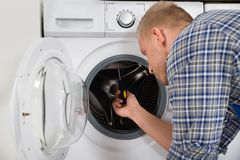 Worker Fixing Washing Machine Stock Photo