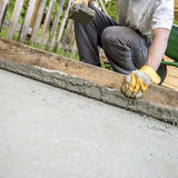 Worker flattening freshly laid concrete Royalty Free Stock Image