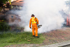 Worker fogging residential area with insecticides to kill aedes Royalty Free Stock Photography