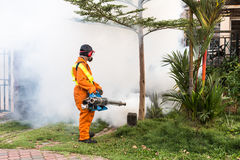 Worker fogging residential area with insecticides to kill aedes Stock Images