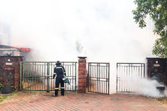Worker fogging residential area with insecticides to kill aedes Stock Photo