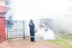 Worker fogging residential area with insecticides to kill aedes Royalty Free Stock Photos