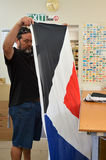 Worker fold the Red Peak flag Stock Photos