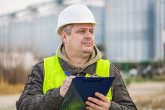 Worker with folder near the factory in winter Stock Photo