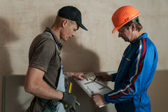 Worker and foreman discuss the scheme plasterboard ceiling Royalty Free Stock Photo