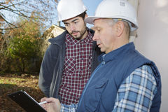 Worker and foreman writes something in clipboard Stock Photography